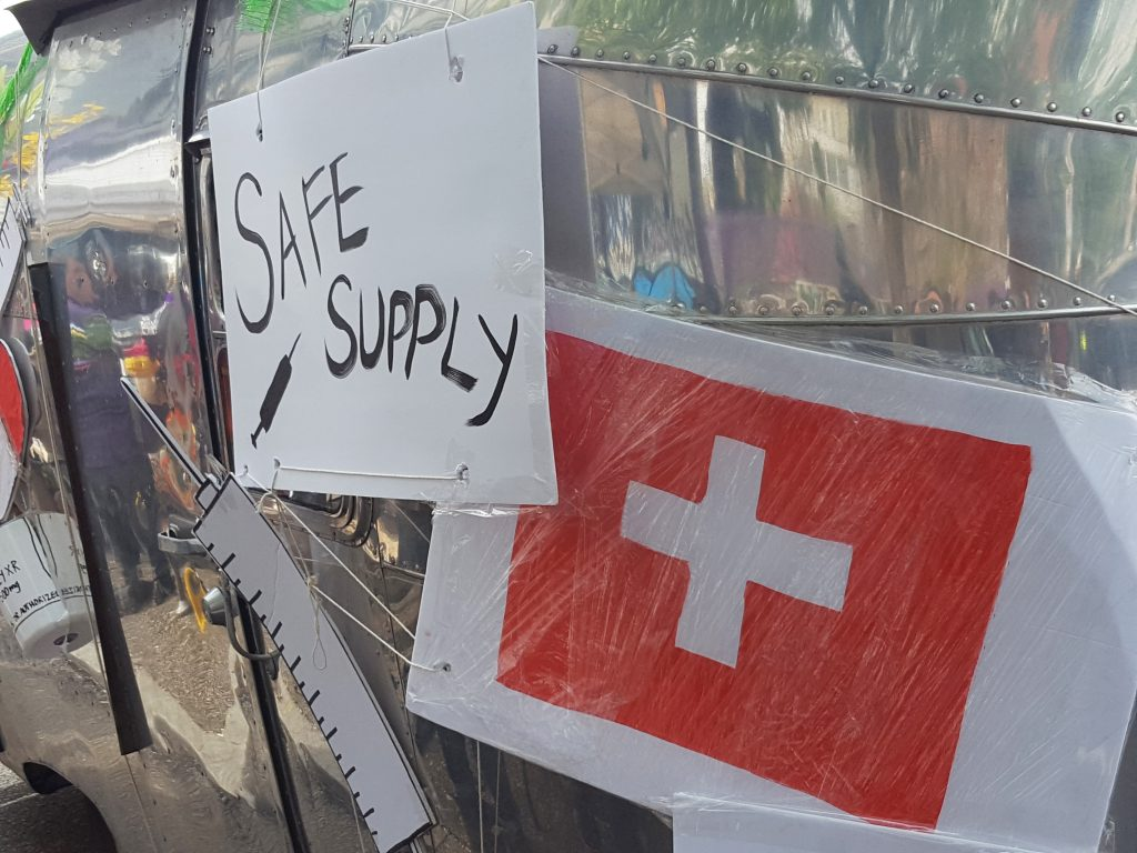 The words safe supply are written on a sign that is attached to a cart made out of metal.