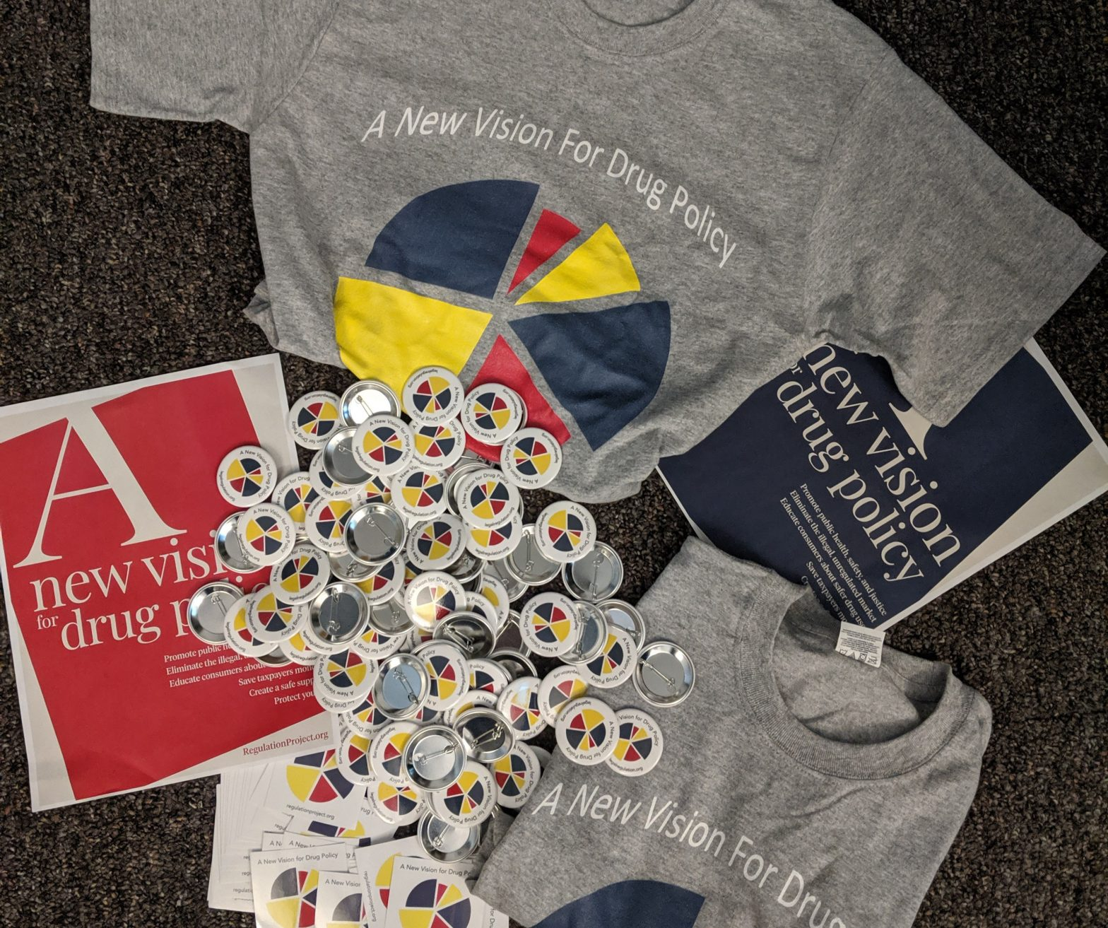 T-shirt, stickers, buttons arranged on the floor